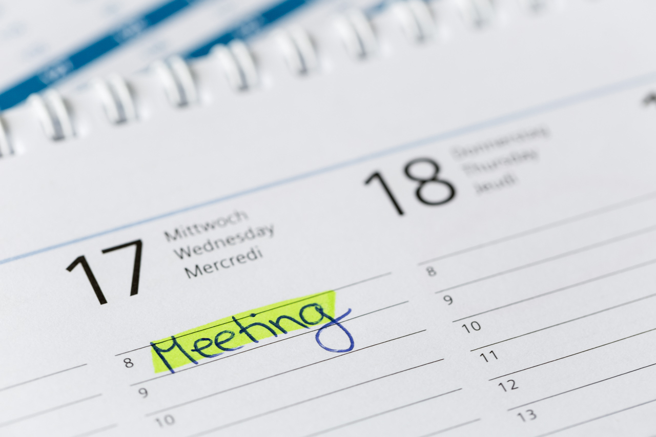 "The word ""Meeting"" written on a calendar."